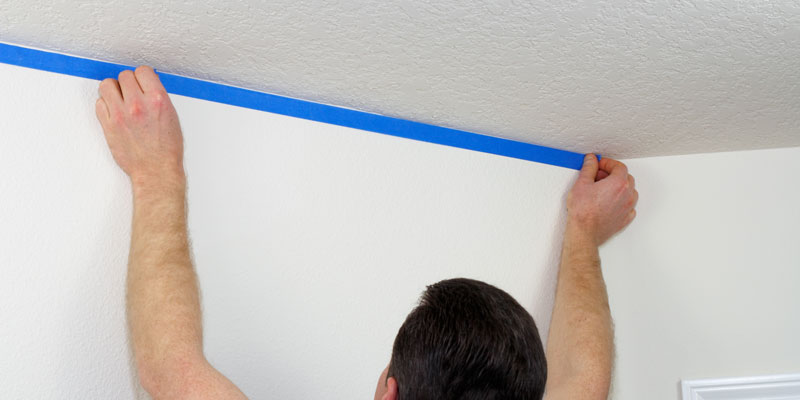 man applying blue painter's tape to wall