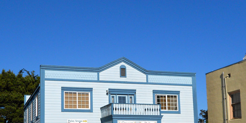small-town shop with balcony painted light blue with darker blue accent with clear blue skies