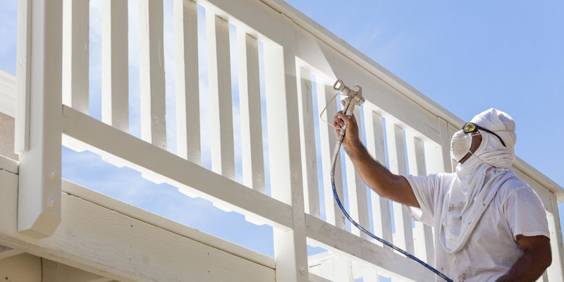 man wearing protective gear spray painting railings of a deck