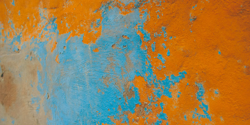 peeling layers of blue and orange paint on wall