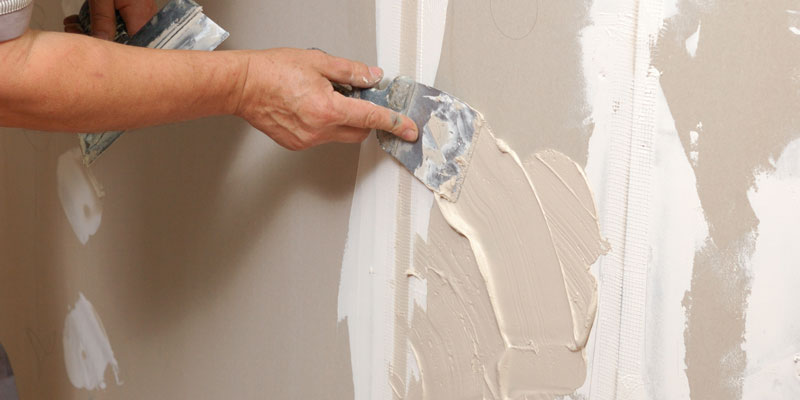 man patching hole in drywall with spackling paste and putty knife