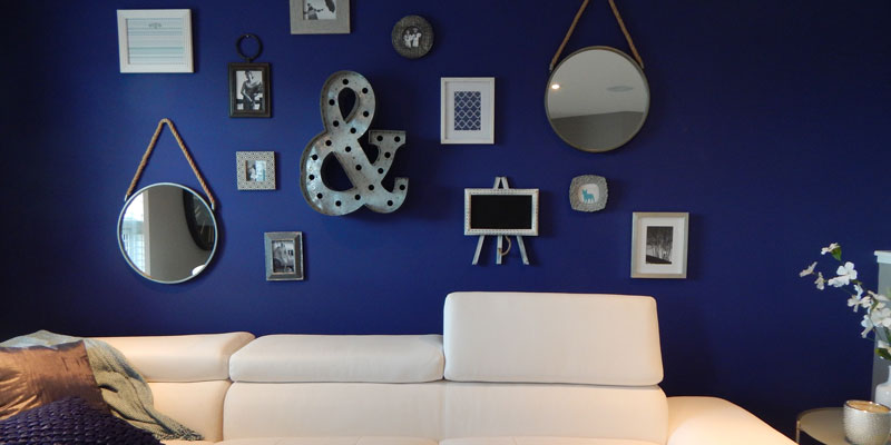 white sofa against boldly blue-painted wall with many wall decorations