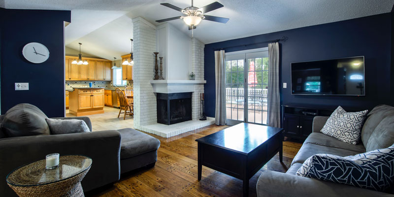 navy-painted living room with sofas and coffee table on wooden floor with fireplace in corner and ceiling fan