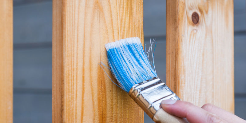 blue-bristled brush applying stain to wooden balcony boards