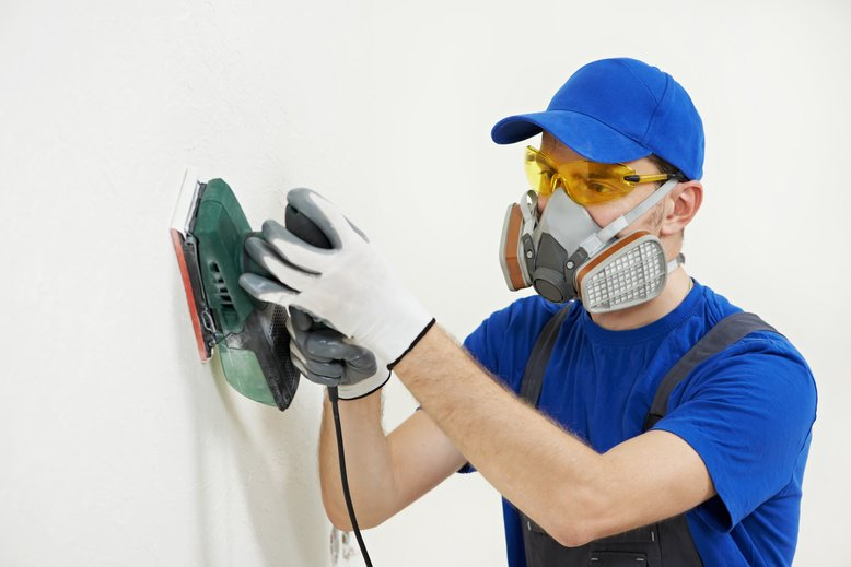 painter wearing a respirator while sanding wall to prepare for painting project