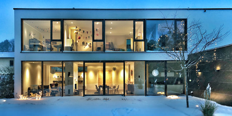 two-story home with flat roof in evening during wintertime