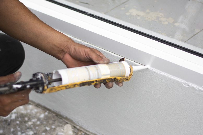 professional painter caulking outside of commercial building