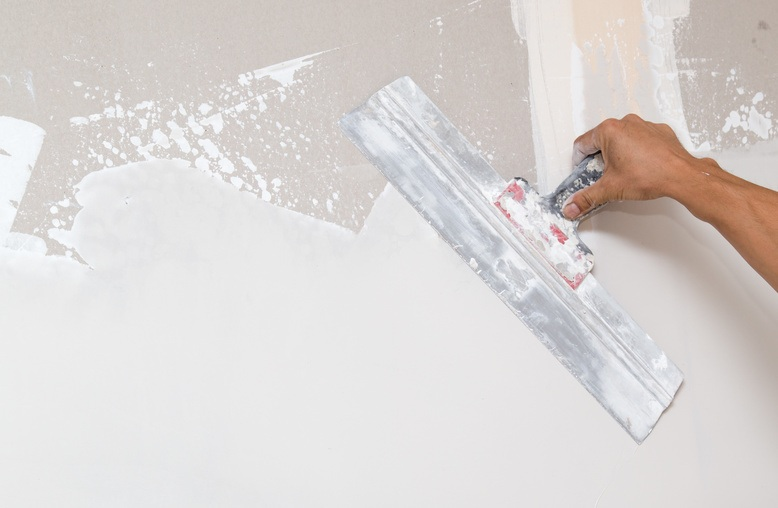 professional painter repairing damaged drywall in commercial building
