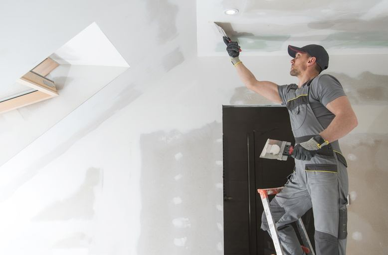 professional painter repairing damaged drywall